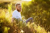 Red-bearded Man Sitting On The Grass