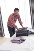 Portrait of confident young businessman unpacking suitcase on bed