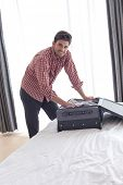Portrait of young businessman unpacking suitcase in hotel room