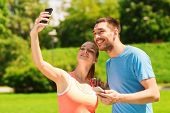 fitness, sport, training, technology and lifestyle concept - two smiling people with smartphones out