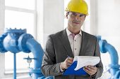 Portrait of young male manager writing on clipboard in industry