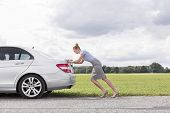 Full length side view of businesswoman pushing broken down car at countryside