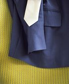 Closeup of a cropped blue suit and tie on yellow surface