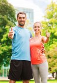 fitness, sport, friendship and lifestyle concept - smiling couple outdoors showing thumbs up
