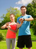 fitness, sport, training, technology and lifestyle concept - two smiling people with heart rate watc