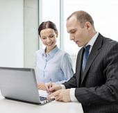 business, technology and office concept - smiling business team with laptop computer and documents h