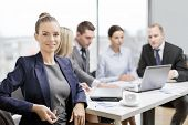 business, technology and office concept - smiling businesswoman with eyeglasses in office with team