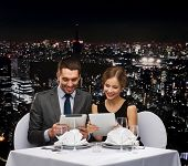 restaurant, couple, technology and holiday concept - smiling couple with menus on tablet pc computer