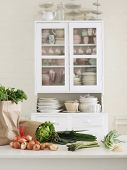 Closeup of fresh vegetables and paper bag on kitchen counter with utensils in cupboard