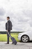 Full length of young businessman with suitcase leaving broken down car at countryside