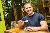 Young fitted man enjoying an organic juice and cereals in a raw restaurant