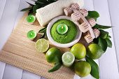 Spa composition with lime and bowl of sea crystals on bamboo mat and color wooden background