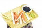 Crab Sticks In Wooden Plate And Table Cloth On White Background