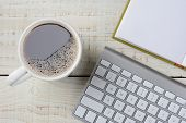 Overhead shot of a fresh brewed cup of coffee, an open book and a computer keyboard on a rustic white wood desk. Horizontal format.