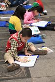 Asian children learning to draw on the ground at a park