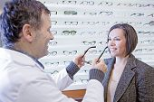 Optician Trying On Glasses To A Customer