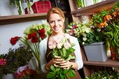 Pretty girl with several pale roses looking at camera in floral shop