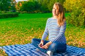 Pregnant Woman Listening To Classical Music In The Autumn Park