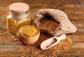 Mustard seeds in bag and Dion mustard in jar and bowl on  wooden background