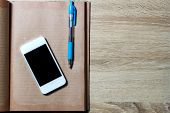 Open Diary And Smartphone On Wooden Background, Top View