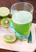 Glass of fresh juice with pieces of lime and kiwi on cut board and wooden table background