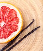 Dried grapefruit with vanilla beans on wooden background