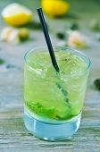 a glass with an appetizing mojito on a rustic wooden table outdoors