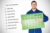 Smiling young mechanic in boiler suit pointing on bcalendar in his hands against green card