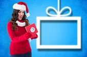 Disappointed brunette opening christmas gift against blurred christmas background
