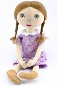 foto of rag-doll  - Rag doll in a purple dress on a white background - JPG