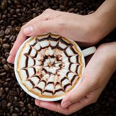 Closeup Of A Beautiful Cup Of  Latte Art In Hand On Coffee Bean Background