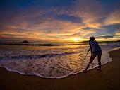 Woman photographer Sunset on the beach of Ao Nang in Krabi Thailand