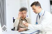 Doctor with elderly woman showing medical prescription