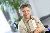 Elderly woman in wheelchair reading book