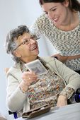 Old woman showing picture to home carer