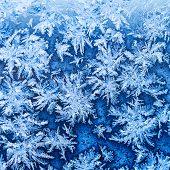 Snowflakes And Frost On Window Glass Close Up