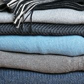 Background With Stack Of Warm Woolen Clothing
