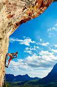 picture of cave woman  - female rock climber climbs on a rocky wall against a blue cloudy sky - JPG