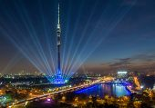 MOSCOW, RUSSIA - OCT 10, 2014: Ostankino Tower with rays around her against the backdrop of the city at night on Moscow International Festival Circle of Light