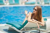 Happy young woman in swimsuit laying on chaise-longue poolside