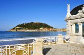 a view of La Concha Beach in San Sebastian, Spain, with the Urgull Hill in the background