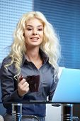 Blonde pretty business woman working at her office. She is very busy and hot.