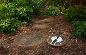 A Worn Sundial Sits At The Start Of A Garden Path