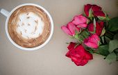 A Cup Of Coffee With Latte Art And Withered Rose On Brown Paper Background