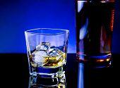 Whiskey Glass Near Bottle On Light Tint Blue Disco