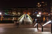 Illuminated Foot Bridge In Over North Dock In Canary Wharf By Night