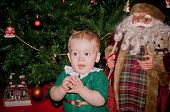 pic of santa baby  - Little baby biy sits under decorated Christmas tree with Santa - JPG