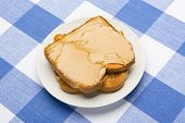 Fresh, hot breakfast toast spread with peanut butter to be consumed during mealtime.