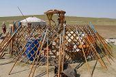 Mongolians assembles yurt in steppe, circa Harhorin, Mongolia.
