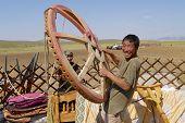 Mongolian man assembles yurt in steppe, circa Harhorin, Mongolia.